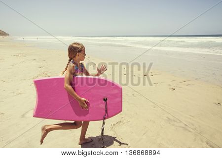 Playing at the beach on summer vacation running into the ocean with a boogie board