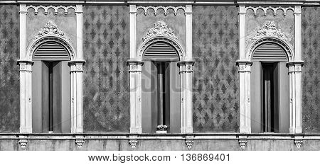 Three windows in Venetian Gothic style of an old Italian palace.