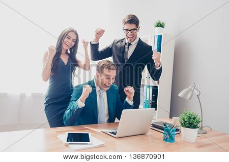 Happy Successful Businesspeople Triumphing With Raised Hands And Looking At Laptop
