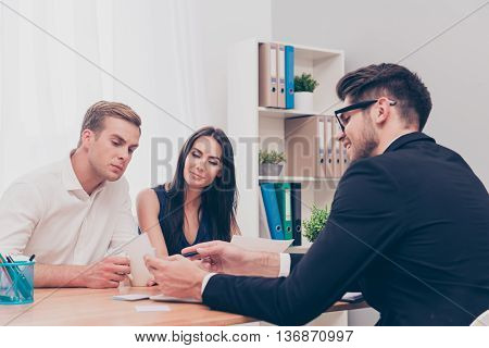 Happy Young Couple On Consultation In Real Eatate Agent