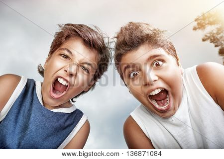 Portrait of a two crazy boys screaming to camera, over grey sky background, allow to enjoy the pleasure of freedom in a summer camp
