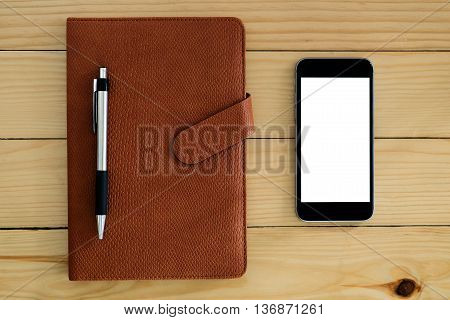 Top view of desk table with blank screen smartphone pen and leather notebook.Office gadgets.Flat lay image