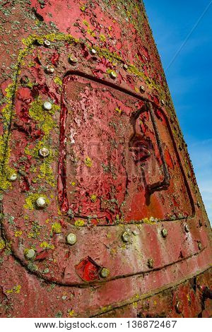 Huge rusty red chnnel marker buoy with steel hatch and green algae