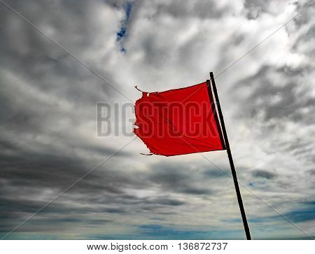The wind blows a torn red flag under cloudy skies