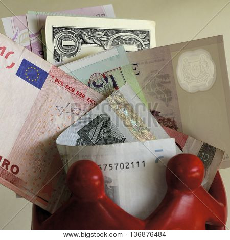 Mixed currency notes surrounded by red figures.