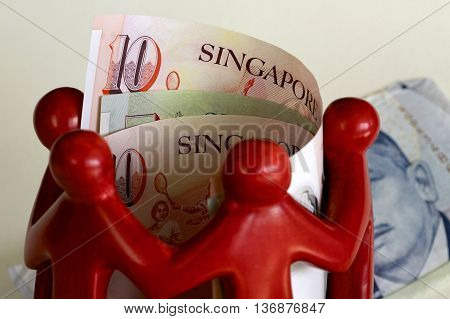 Some Singaporean notes surrounded by red figures.