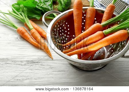 Carrots in colander on wooden table