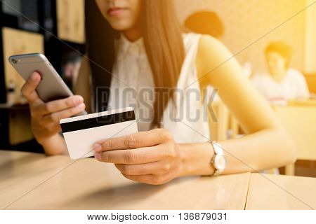 Woman hands holding a credit card and using smart phone for online shopping