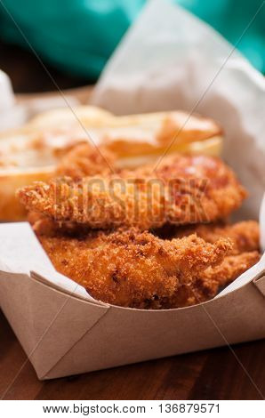 breaded chicken fingers and fries in a take out container