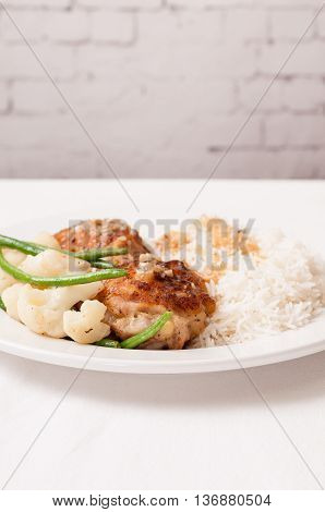 crispy fried chicken thighs with vegetables over rice in a lemon sauce