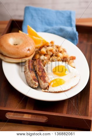 sunny side up eggs with english banger sausages and hashbrowns and a bagel