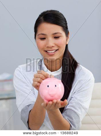 Asserive businesswoman saving money in a piggybank in the office