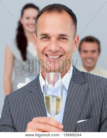 Cheerful businessman toasting with Champagne with his team in the background