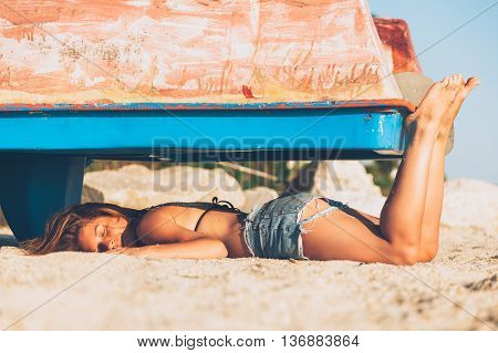 Young hipster woman lying on the sand beach under the old paddle boat