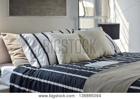 Offwhite And Striped Pillows On Bed With Deep Blue Striped Blanket In Modern Style Bedroom
