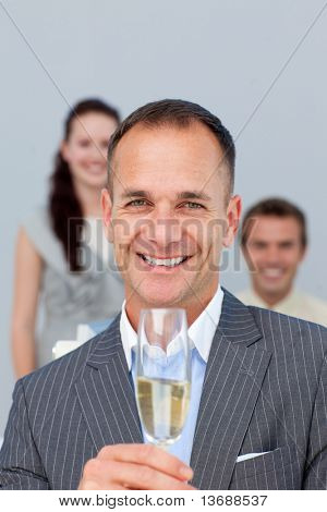Successful businessman holding Champagne with his team in the background
