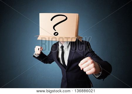 Businessman standing and gesturing with a cardboard box on his head with question mark