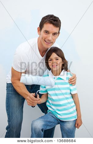 Smiling Father and his boy painting a room in their new house