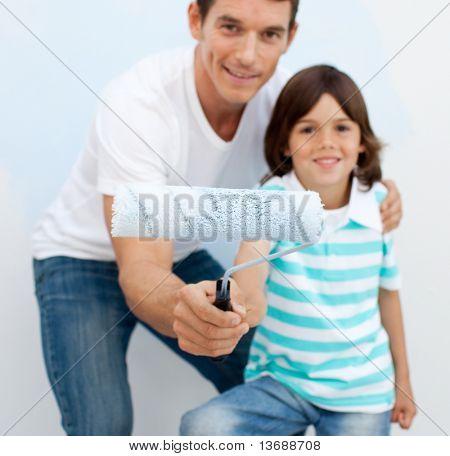 Glückliche Vater und sein Sohn mit einen Pinsel