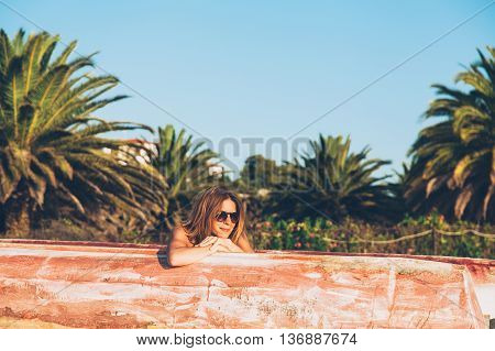 Smiling hipster woman outdoor portrait, sitting in the old paddle boat