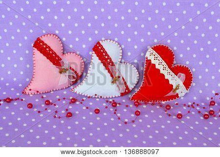 White, pink and red felt heart decorated with lace and a small metal key. Three felt hearts on a lilac background. Valentine's day crafts and gifts. Wedding crafts and gifts