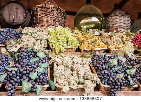 Different varieties of grapes in the wicker baskets. Market place. Healthy food.