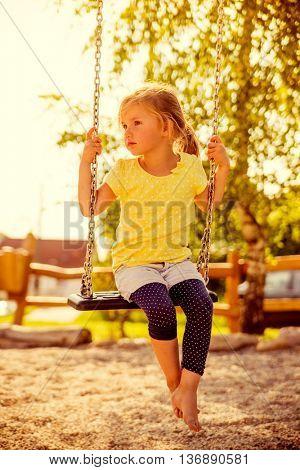 little girl swings while sun set