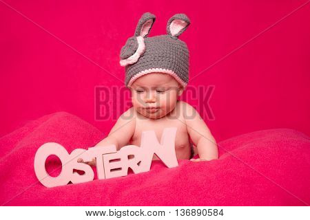 little cute easter baby playing with german letters