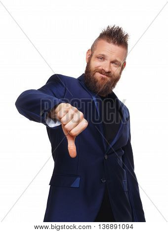Man gesturing thumb down sign isolated at white. Young stylish hipster with beard in blue suit showing negative emotion. Sarcastic male portrait symbolising loss and failure, disapproving something.