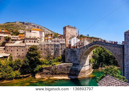 MOSTAR, BOSNIA AND HERZEGOVINA-JULY 20, 2014: Unidentified tourists stroll across of the Old Bridge (Stari Most) in Mostar on a sunny day. Old Bridge is UNESCO World Heritage Site. Mostar is situated on the Neretva River.