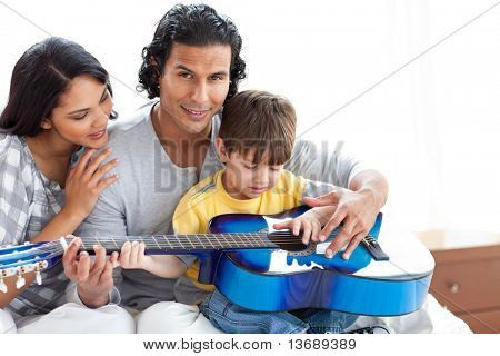 Cute little boy playing guitar with his parents at home