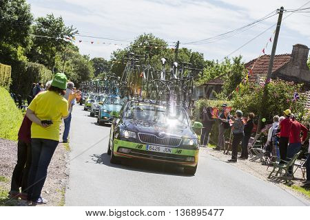 Documentary editorial. Hautteville Bocage, Manche, France - July 2 2016. First step of the French Cycle Tour, Cycle men and supporters along the road. Publicity cars before the cyclists
