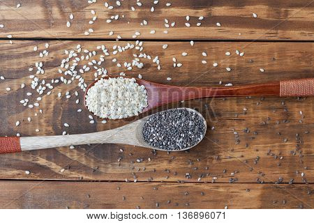 Sesame Seeds And Black Chia Seeds In Wooden Spoons