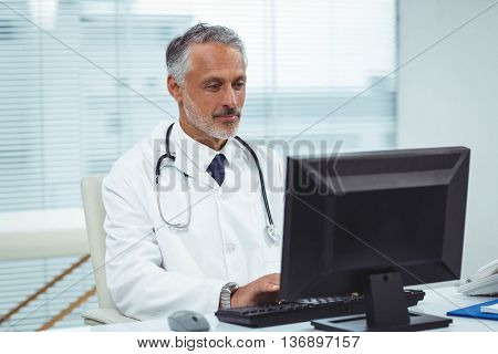 Doctor typing on his computer in cabin