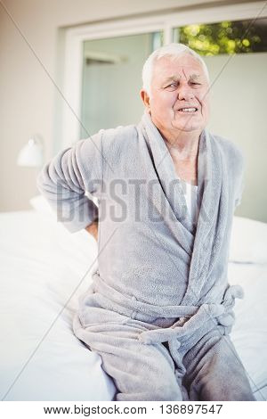 Portrait of senior man grimacing from back pain while sitting on bed