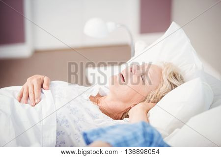 Senior woman snoring next to husband on bed at home