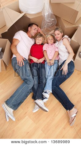 Tired family sleeping lying on the floor while moving house
