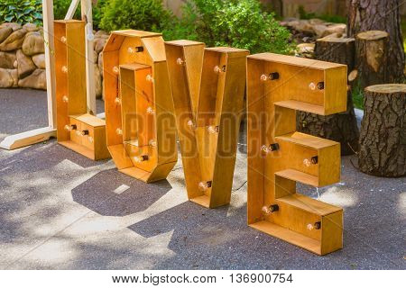 Word love consisting of the letters highlighted with bulbs standing in the park