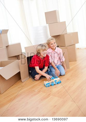 Smiling sibling playing with a train while moving house