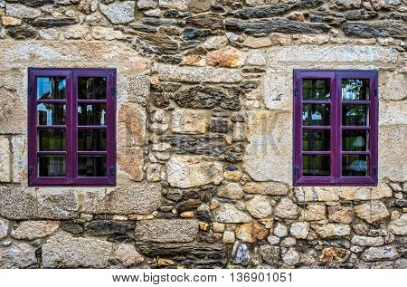 Purple window on medieval castle made of stone and rocks. Architectural textures of exterior of old building in Santa Cruz island Oleiros Rias Altas A Coruna Spain.