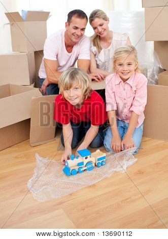 Cute children playing with a train while moving house