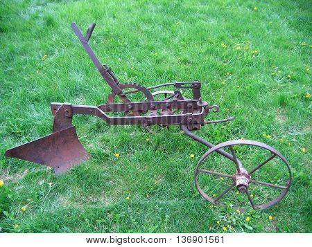 The old farm hand plow on the background of green grass.