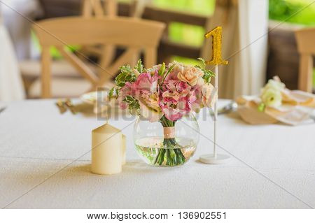 Stylish beautiful luxury wedding decor with a lot of flowers, candles and number on the tables in restaurant hall