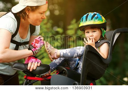 Young woman on a bicycle with little daughter