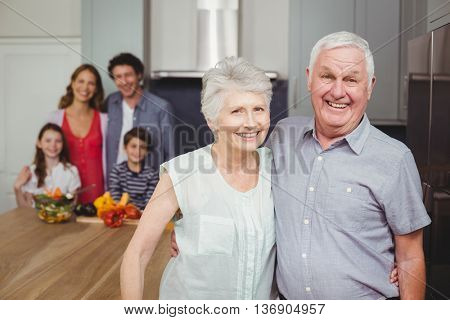Portrait of smiling grandparents standing with family in kitchen at home