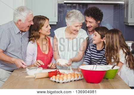 Smiling grandmother cooking food with family in kitchen at home