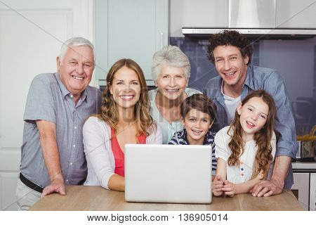 Portrait of smiling happy family with laptop in kitchen at home