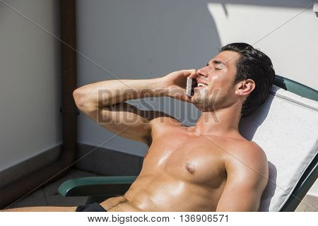 Shirtless Young Man Drying Off in Hot Sun Talking on Cell Phone, Muscular Man Wearing Bathing Suit Sunbathing on Beach Lounge Chair, Eyes Closed