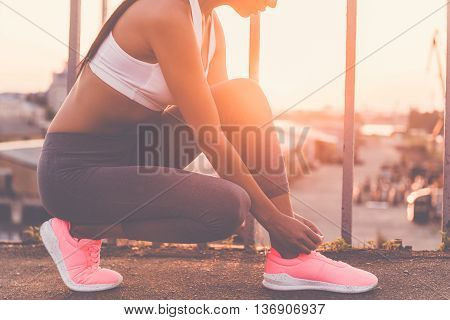 Preparing to run. Close-up of beautiful young woman in sports clothing tying her shoelaces while standing on the bridge with evening sunlight and urban view in the background