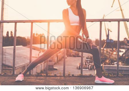 Warming up before jogging. Cropped image of beautiful young woman in sports clothing doing stretching exercises and looking concentrated while standing on the bridge
